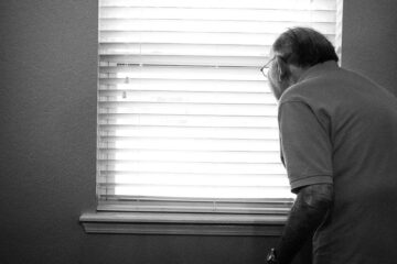Perennial Seniors on Campus - Picture of an elderly man looking out of a window, photo in black and white